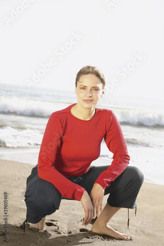 Portrait of woman kneeling in sand