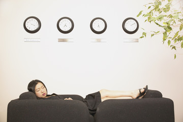 Businesswoman sleeping on couch in office
