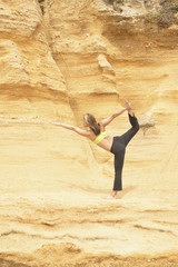 Woman stretching by rock cliff