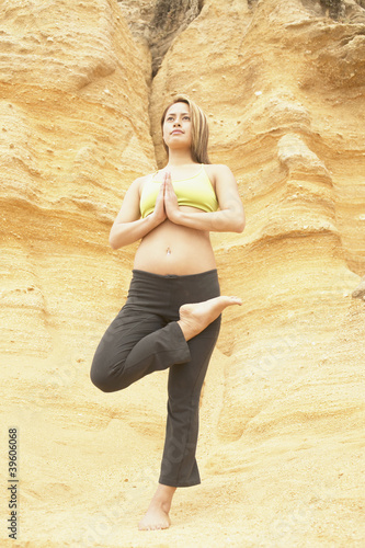 Young woman standing on a rock doing yoga
