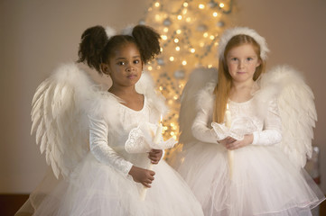 Portrait of two girls dressed as angels