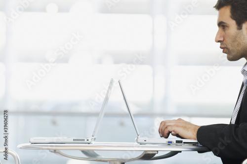 Profile of man typing on laptop