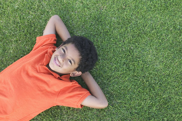 Portrait of boy laying on grass