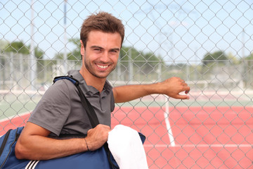 Man with sports bag stood by clay tennis court