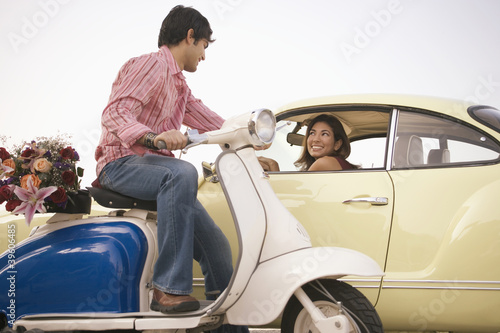 Man on scooter talking to woman in car