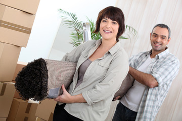 Couple with rolled up carpet surrounded by boxes