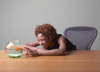 Woman watching goldfish in bowl
