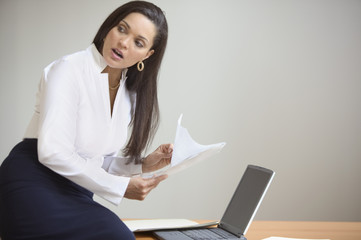 Businesswoman with laptop and paperwork
