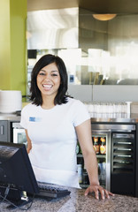 Portrait of teenage girl cashier in restaurant