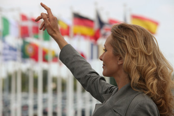 Woman hailing a taxi in front of international flags