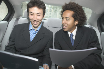 Two businessmen working in backseat