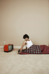 Young man in a sleeping bag next to TV