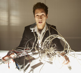 Businessman puzzling over a nest of wires