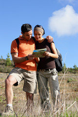 young couple walking through nature consulting map