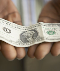 Close up of man holding dollar bill