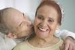 Elderly man kissing wife on the cheek