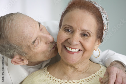 Elderly man kissing wife on the cheek