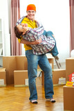 Young couple having fun while moving to new house