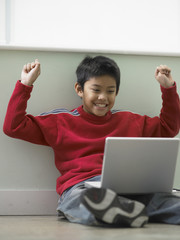Young boy celebrating while using a laptop