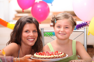 Cheerful woman and little girl celebrating birthday