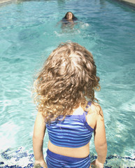 Young girl sitting at edge of swimming pool