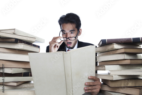 Shocked businessman reading books