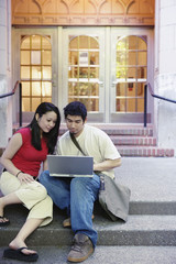 Couple outside sharing laptop