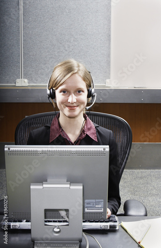 Businesswoman using headset and computer