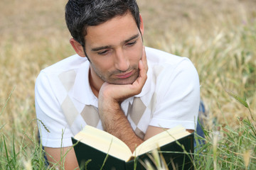 young man lying on the grass and reading a book