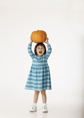 Girl holding pumpkin over head