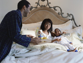 African American father bringing breakfast in bed to mother and son