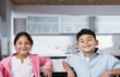 Boy and girl sitting together in kitchen