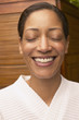 Woman in spa robe smiling with eyes closed
