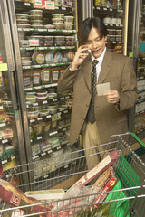 Asian businessman on cell phone in grocery store