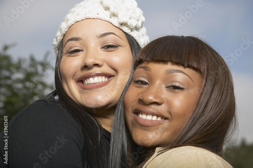 Two African American women smiling and hugging