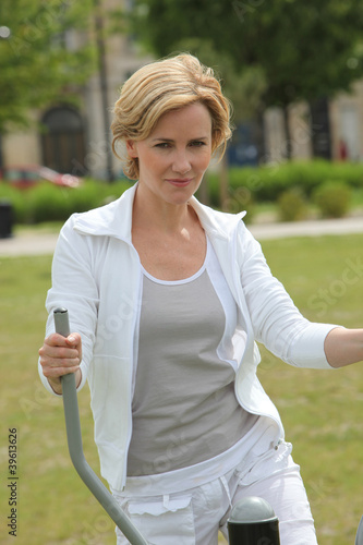 Woman in park on exercise bike