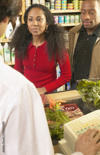 African American couple at check out counter in grocery store