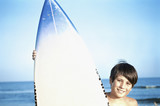 Boy posing with surfboard at the ocean