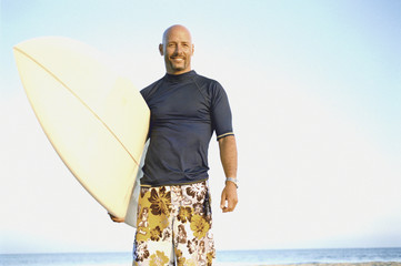 Man posing on the beach with his surfboard