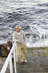 Man standing on stairs by the sea