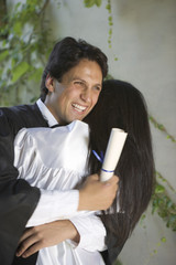 Graduating man and woman hugging each other