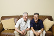 Portrait of elderly men sitting on couch laughing