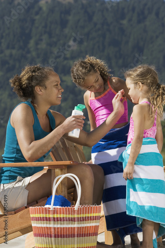 Mother applying suntan lotion to daughters at beach