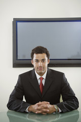 Businessman seated in front of flat screen