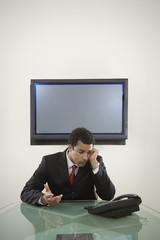 Young businessman staring at his telephone
