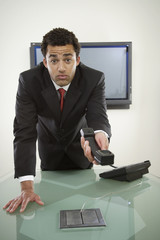 Perplexed businessman holding telephone
