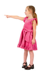 Small nice girl in pink dress pointing  and looking upwards on w