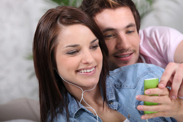 Young couple with a personal music player
