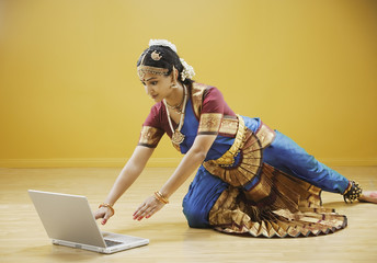 Exotic woman reaching for laptop computer