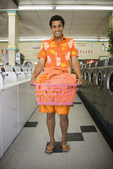 Portrait of man standing in laundromat with laundry